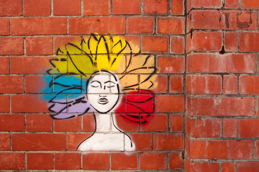 Street art graffiti in spray paint on a red brick wall of a woman with closed eyes, African-American features, and afro hairstyle shaped like flower petals in a rainbow color. This shows zen mindfulness.