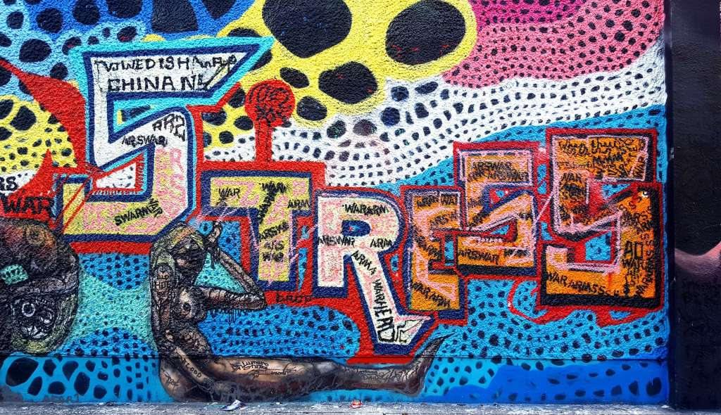 Textured 3D looking street art graffiti mural on a wall in Florida, USA that shows multiple, colorful honeycomb artistic circles in a lace pattern with the word Stress written in large letters across it with smaller words written inside showing stressors such as war, arms, guns, swarms, China. There is a woman painted underneath with her hand to her head signifying she has been thinking about these thing and that she has a headache.
