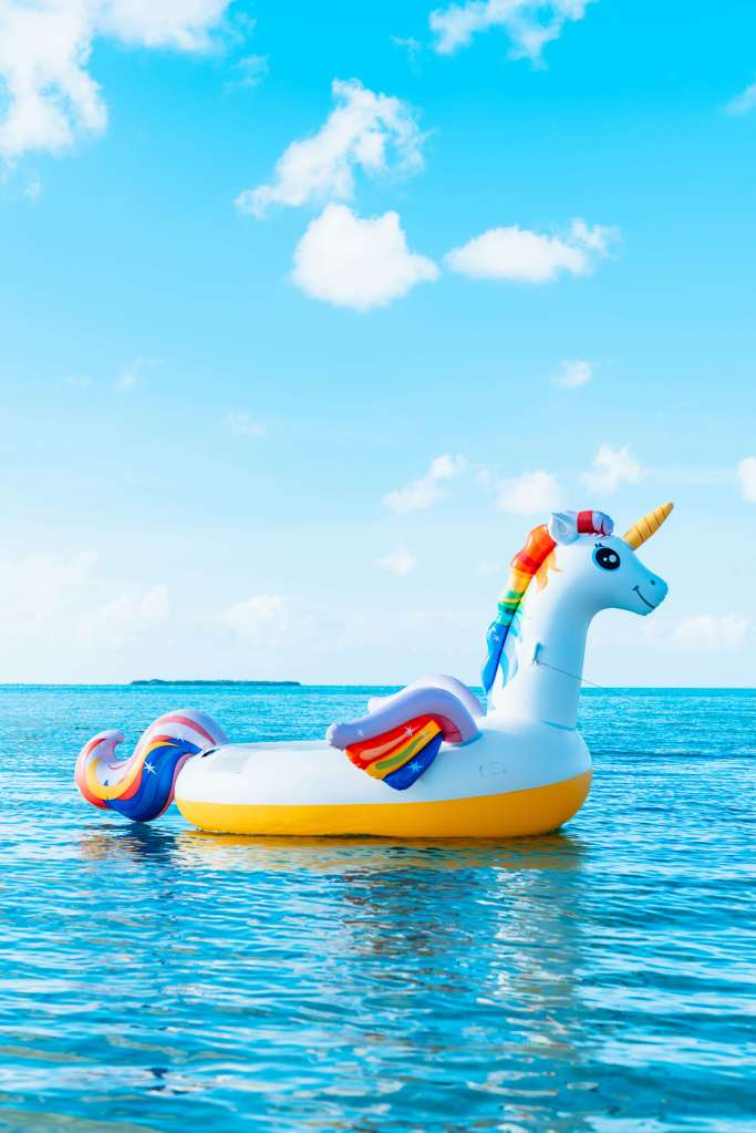 A colorful, happy, inflated rainbow unicorn floating in the ocean, sea, or river with beautiful sparkling cerulean blue water during the daytime on a bright, sunny day with fluffy white clouds in the sky.