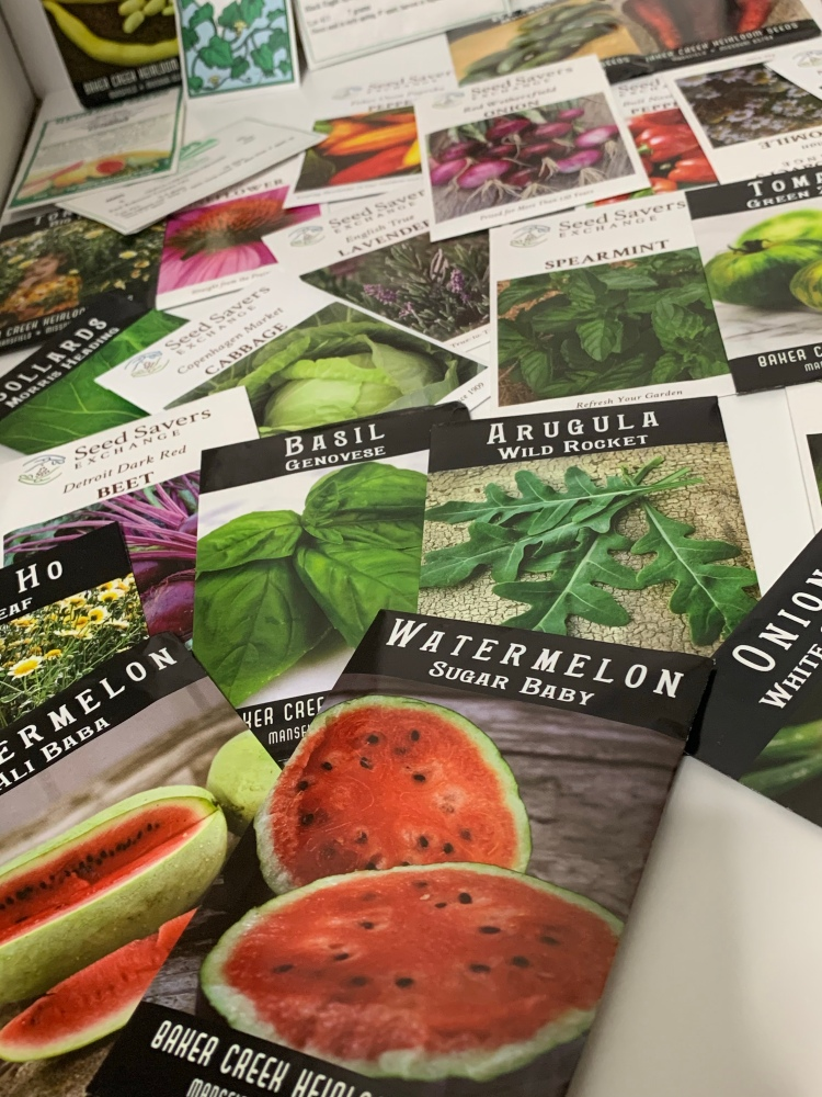 Several packets of organic, heirloom, open-pollinated, and non-GMO herb and plant seeds.