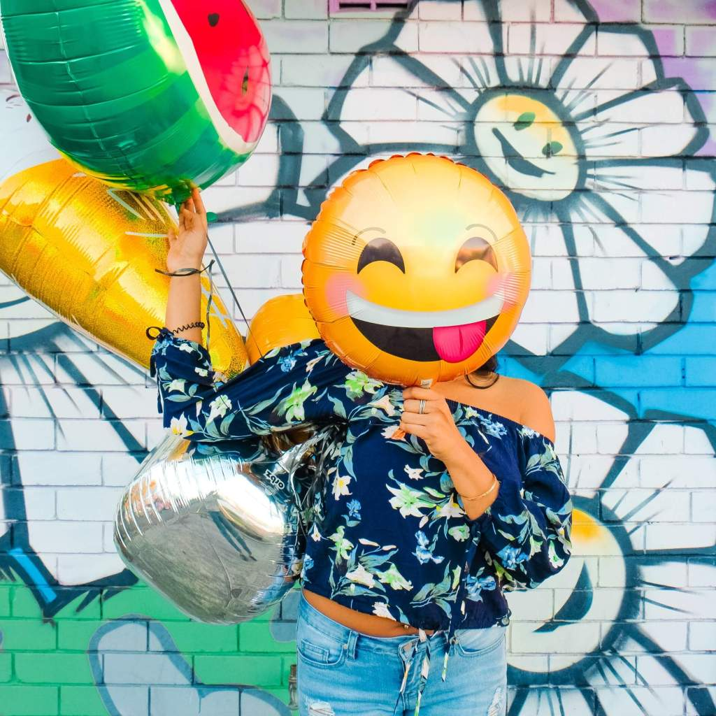 Woman standing in front of blue wall with graffiti street art of white flowers. She's holding several  helium ballons and one with a smiley face with tongue hanging out is in front of her face