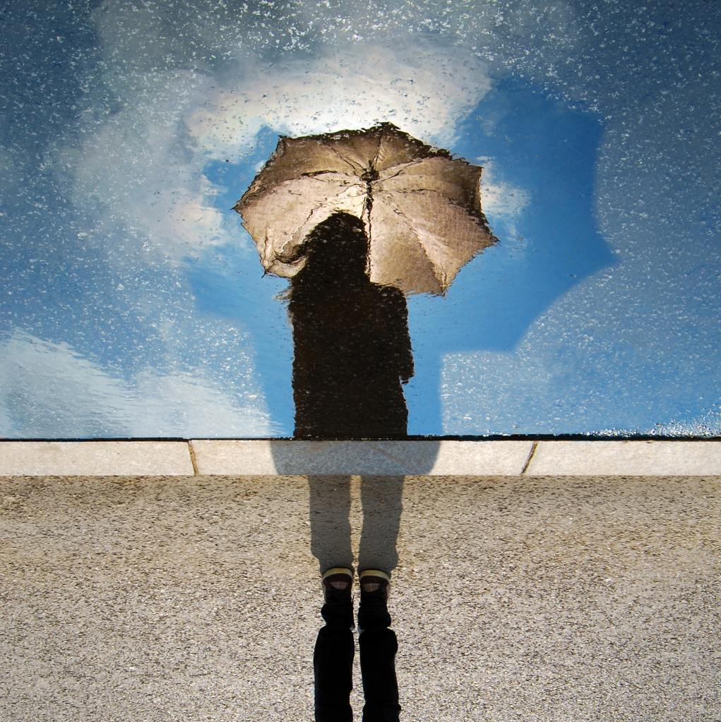 Feet firmly planted on the ground, or head in the clouds: woman holding umbrella on a sunny day looking into a puddle.